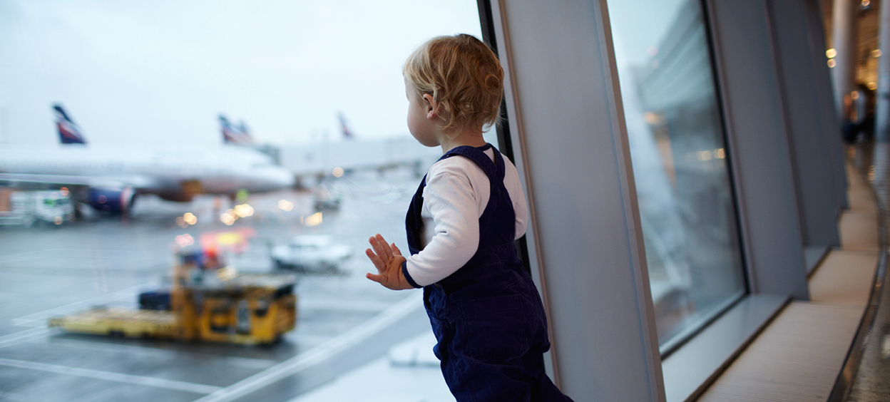 Child looking out from the airport lounge